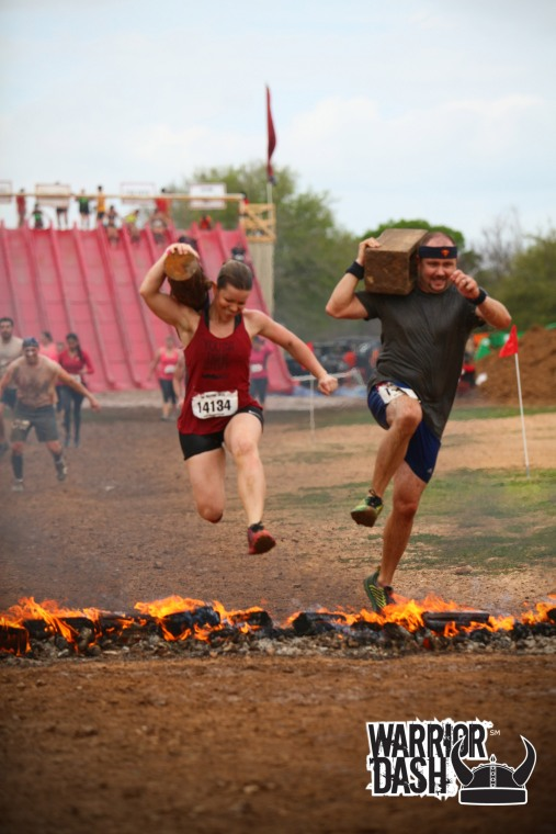 Ryan & I jumping the fire at Warrior Dash with our toys in tow. We carried these the entire race.